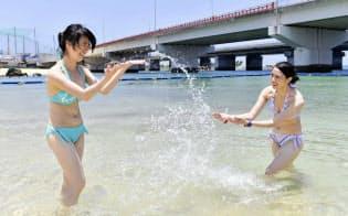 那覇市で、海水浴を楽しむ海外からの観光客=共同