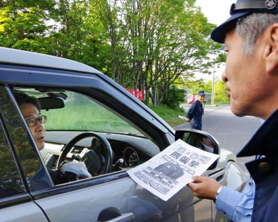 青森県警が行った、クマへの注意を呼び掛けるチラシの配布(11日、青森県新郷村)=共同