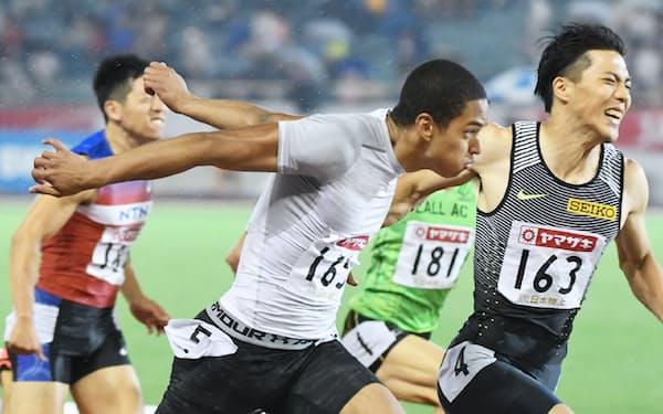 男子100メートル決勝で優勝したケンブリッジ飛鳥。右は2位の山県(25日、名古屋市のパロマ瑞穂スタジアム)