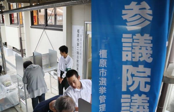 高校には地域の有権者も訪れ、投票所の入り口で宣誓書の記入の案内をする男子生徒