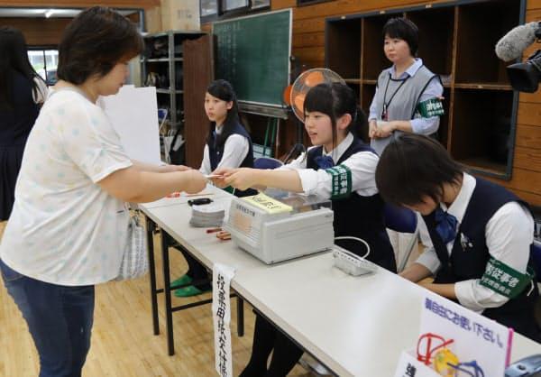 上田帆夏さん(17、中央)は「間違わないように」と心がけ、投票用紙の交付係を務めた