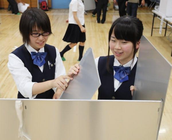 投票が終わり、ほっとした様子で投票記載台の片付けをする高校3年生の田中涼海さん(17、左)と上田帆夏(17)さん
