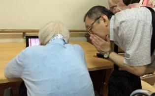 歌舞伎の映像を見る高齢女性(左)に説明する薮内さん(大阪市)