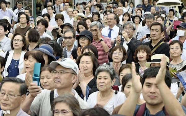 候補者の街頭演説を聞く大勢の人たち(6月27日、横浜市中区)=共同