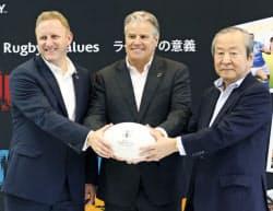 ワールドラグビーのブレット・ゴスパーCEO(中央)とポーズをとる日本大会組織委の嶋津昭事務総長(右)ら(30日、東京都北区)=共同