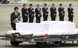 犠牲者のひつぎに献花する岸田外相(左)(5日午前、羽田空港)