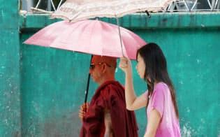日傘を手にサングラス姿で歩く僧侶(左)。カジュアル衣料品店の袋を携える腕には虎の入れ墨が