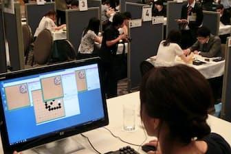 手前が「パンダ先生」の画面。奥のブースが棋士のペア。囲碁AIは詰め碁の問題を解くスピードと正確さでプロ棋士らを上回った。