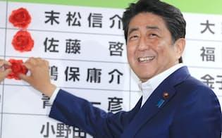 当選のバラを付けて笑顔を見せる安倍首相(10日夜、自民党本部)