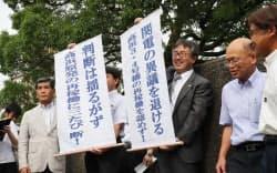 大津地裁前で「関電の異議を退ける」と書かれた垂れ幕を掲げる弁護士ら(12日午後、大津市)