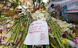 テロ犠牲者追悼のため現場近くにささげられた花束やメッセージ(8日、バングラデシュのダッカ)=共同