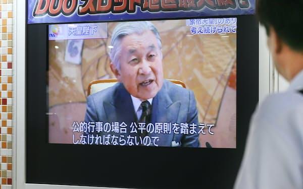 天皇陛下の生前退位の意向を伝えるテレビのニュースを見る人(13日、東京・有楽町)