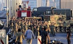 16日、トルコ・イスタンブールのボスポラス海峡に架かる橋で、手を上げ投降する兵士ら=ゲッティ共同