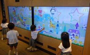 日本マクドナルドの「デジタルプレイランド」には触ると絵が動く大画面モニターが備わる(東京・大田)