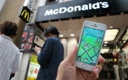 マクドナルドの店先で「ポケモンGO」で遊ぶ人たち(7月、東京・渋谷)