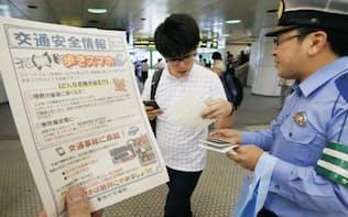 「ポケモンGO」の配信が始まり、歩きスマホへの注意を呼び掛ける警察官(22日午後、東京都新宿区)