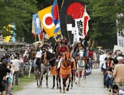 相馬野馬追が始まり、相馬中村神社から出陣する騎馬武者の行列(23日、福島県相馬市)=共同