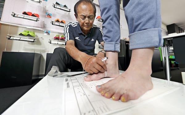甲回りなどを測り、専用用紙に足型の情報を書き込んでいく