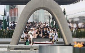 原爆慰霊碑に向かい祈りをささげる人たち(6日午前、広島市の平和記念公園)=写真 三村幸作