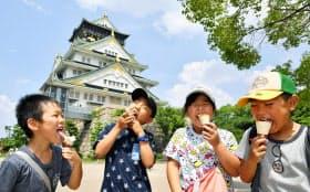 厳しい暑さとなった大阪城公園で、アイスクリームを食べる子どもたち(5日午後、大阪市)=共同