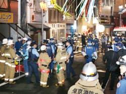 事件があった商店街を調べる警察官や消防隊員ら(7日夜、東京都杉並区)=写真 目良友樹