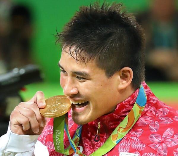 金メダルをかみ、笑顔を浮かべる