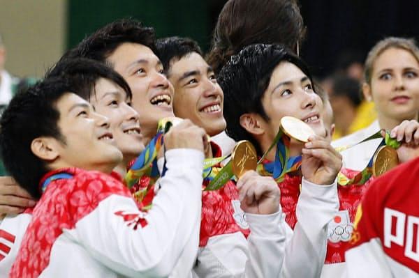 体操男子団体総合で優勝し、金メダルを手に笑顔の(左から)山室光史、内村航平、田中佑典、白井健三、加藤凌平=共同