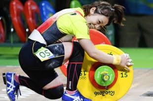 重量挙げ女子48キロ級、ジャークで107キロに成功し、バーベルをなでて喜ぶ三宅宏実=共同