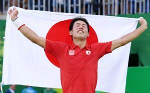 テニス男子シングルで銅メダルを獲得し日の丸を掲げる錦織=写真 柏原敬樹
