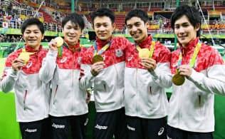 男子団体総合の金メダルを手に笑顔の(左から)山室、内村、田中、白井、加藤=共同