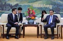 25日、北京の人民大会堂で谷内正太郎・国家安全保障局長と対談する李克強首相(右)=AP