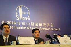 中国石油化工の王董事長(右)は原油相場について厳しい見通しを示した(29日、香港)