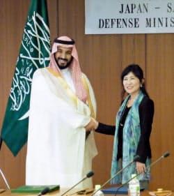 会談前、握手を交わすサウジアラビアのムハンマド・ビン・サルマン副皇太子兼国防相(左)と稲田防衛相(2日午後、防衛省)=共同