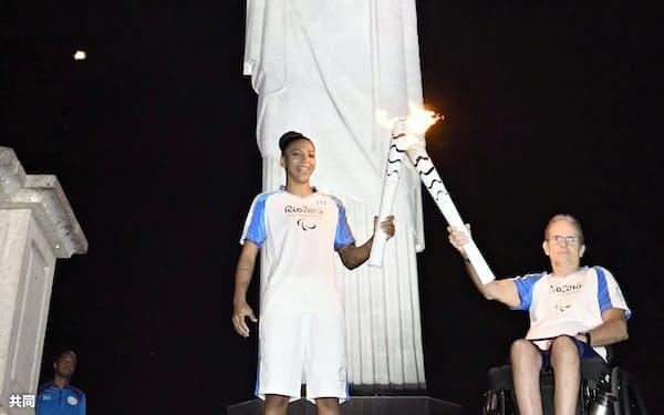 コルコバードの丘に立つキリスト像の前でつながれる聖火。左は柔道女子57キロ級で金メダルを獲得したブラジルのラファエラ・シルバ選手(6日、リオデジャネイロ)=共同