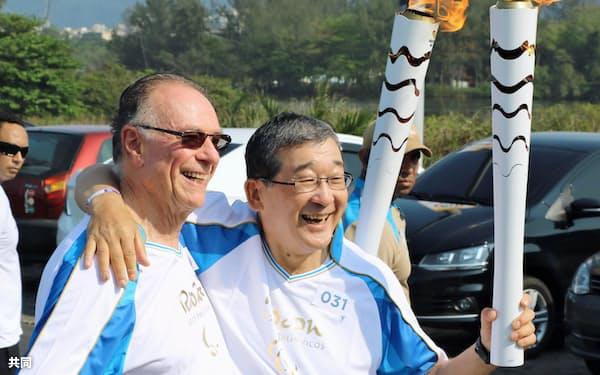 リオ大会組織委のヌズマン会長(左)から聖火を引き継いだ、JPC委員長で東京大会組織委副会長の山脇康氏(7日、リオデジャネイロ)=共同