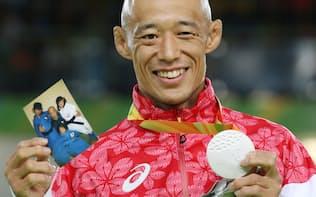 柔道男子60キロ級で銀メダルを獲得し家族の写真を手に笑顔の広瀬誠=寺沢将幸撮影