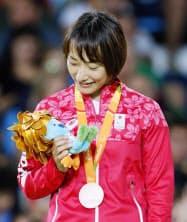 女子57キロ級で銅メダルを獲得し、表彰台でマスコットを見つめる広瀬順子=リオデジャネイロ(共同)