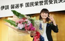 国民栄誉賞の受賞が決まり、記者会見で花束を手に笑顔の伊調馨選手(13日、東京都新宿区)=浅原敬一郎撮影