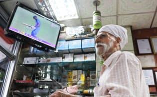 インド料理店で立ったままクリケットの中継を見つめる男性