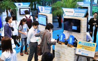 「フィンテック・サミット」が開幕し、展示イベントで最先端のサービスを体験する人たち(20日午前、東京・丸の内)