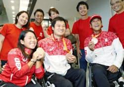リオデジャネイロ・パラリンピックから帰国し、笑顔でメダルを手にする車いすテニスの(手前左から)上地結衣選手、国枝慎吾選手、斎田悟司選手(22日、成田空港)=共同
