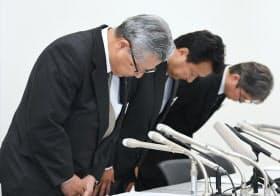 記者会見で頭をさげる電通の中本副社長執行役員(左)ら(23日午後、東京都中央区)