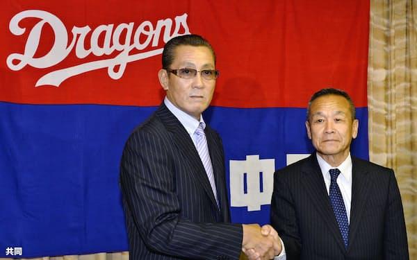 就任記者会見を終え、プロ野球中日の佐々木崇夫球団社長(右)と握手する森繁和新監督(29日午後、名古屋市)=共同
