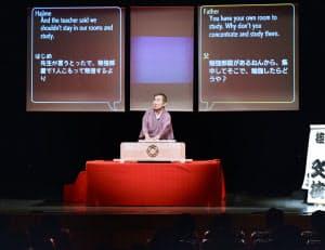 日本語と英語の字幕を背に落語を演じる桂文枝(大阪市浪速区の朝日劇場)