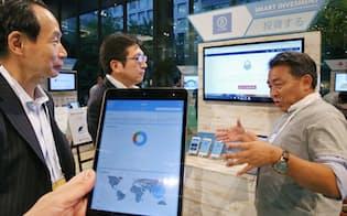 「フィンテック・サミット」で資産運用のロボアドバイザーについて説明するエイト証券のブース(20日、東京・丸の内)