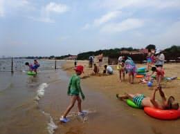 海水浴客でにぎわう北戴河のビーチ。奥の柵から先は共産党指導者専用で立ち入り禁止に