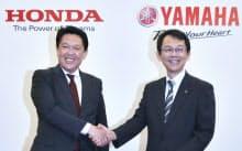 二輪車の生産、開発の提携を発表し、握手するホンダの青山真二取締役(左)とヤマハ発動機の渡部克明取締役(5日午後、東京都港区)