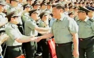 新設した「戦略支援部隊」を視察し、幹部一人一人と握手する習近平国家主席(8月29日、国営中国中央テレビの映像から)