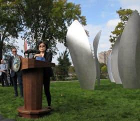 作品への思いを述べるオノさん。右手が作品「スカイ・ランディング(高さ3.7メートル、幅1.5メートル)」(米シカゴ)=野毛洋子撮影