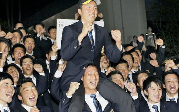 ソフトバンクから1位指名され、チームメートに肩車される創価大の田中正義投手(20日、東京都八王子市)=共同